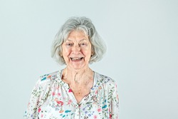 Elderly woman in her 80's with Gray hair isolated on a white backdrop smiling and laughing and happy.