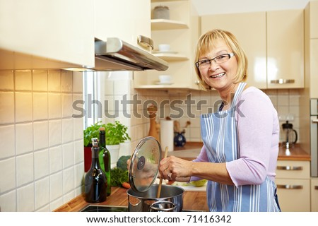 Elderly woman in kitchen on a stove cooking soup