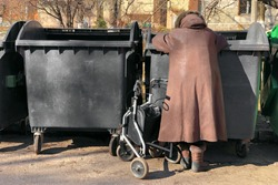 elderly woman in winter coat is looking for food in street garbage cans. disabled grandmother is rummaging for some food in garbage. poverty among the elderly