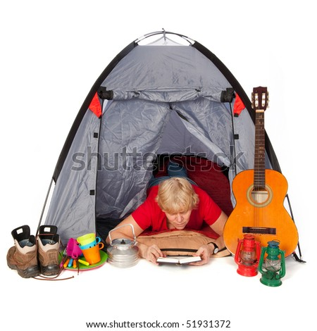 Elderly woman is reading a book in the tent on the campground
