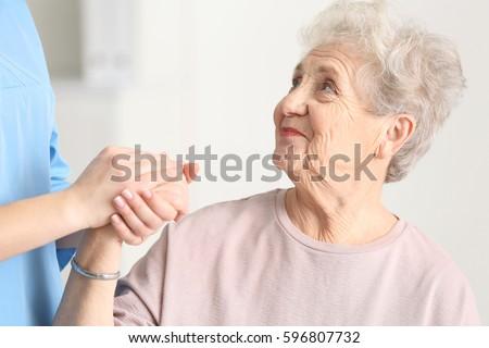 Elderly woman listening doctor in light room