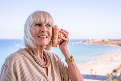 Elderly woman listening to the sound of a conch shell. The woman is dressed in a beige dress and has straight blonde hair