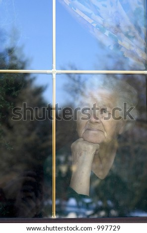 elderly woman looking through the window.