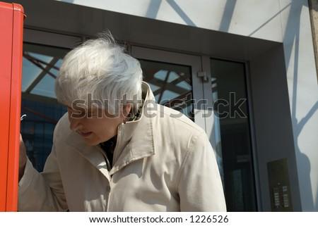 elderly woman looks in letter box