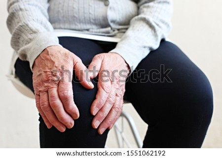 Elderly woman massaging the knee easing the aches. Joint pain concept. Senior old lady experiencing severe arthritis rheumatics pains, massaging, warming up arm. Close up, copy space, background Foto stock ©