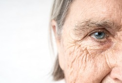 Elderly woman old eye and wrinkled face. Fragment of the portrait. Copy space.