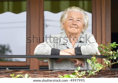Elderly woman on the porch of her house.