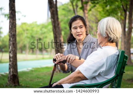 Elderly woman or mother with depressive symptoms, alzheimer patient,asian female caregiver or daughter holding elderly patient's hand comforting,support in outdoor park feeling sad,depression concept