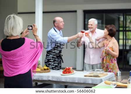 Elderly woman photographing a group of senior having a toast