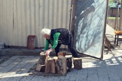 Elderly woman preparing timbers for stove. Selective focus