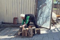 Elderly woman preparing timbers for stove. Selective focus