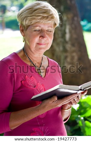 elderly woman reading bible in the garden
