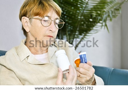 Elderly woman reading warning labels on pill bottles with medication