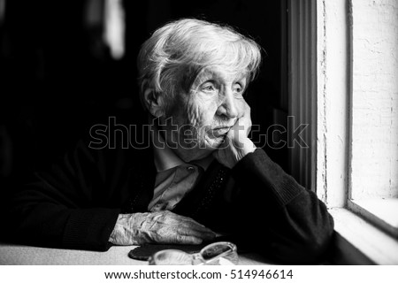 Shutterstock Elderly woman sadly looking out the window, a black-and-white photo.
