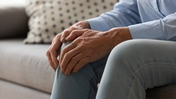 Elderly woman seated on couch touches knee suffers from repeated painful feelings on knee pain related to aging process close up image, tendonitis and arthritis diseases, joint degeneration concept
