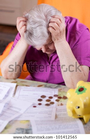 Elderly woman sits in front of papers and desperate