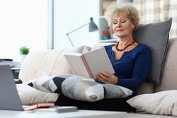 Elderly woman sits on sofa at home and reads book. Woman indulges in memories. View old photo albums and recall past times. Learning instructions for using laptop. Positive emotions from good memories
