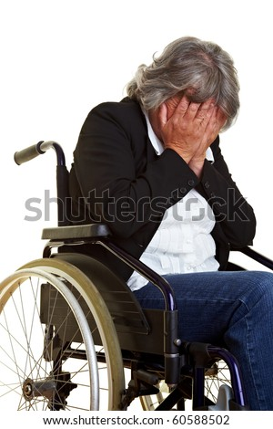 Elderly woman sitting in a wheelchair and crying
