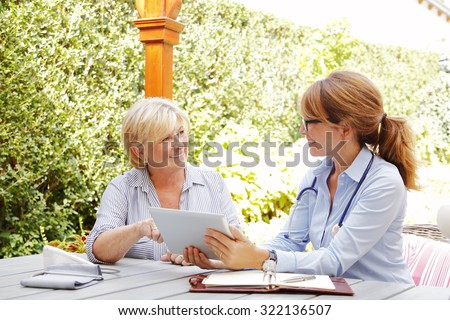 Elderly woman sitting in the garden with home health care nurse and consulting. Middle age caregiver holding in hand digital tablet and giving advice to her patient.