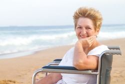elderly woman sitting on wheelchair on beach