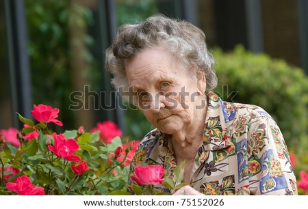 Elderly woman smelling flowers outside during spring