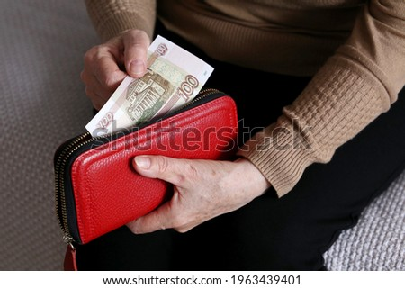 Elderly woman takes out russian rubles from her wallet, wrinkled female hands closeup. Concept of poverty in Russia, pension payments, pensioner