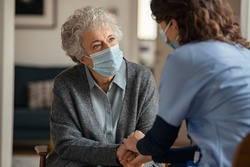 Elderly woman talking with a doctor while holding hands at home and wearing face protective mask. Worried senior woman talking to her general practitioner visiting her at home during virus epidemic.