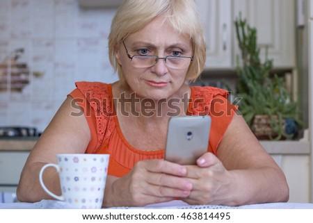 Elderly woman texts on cellar phone Zdjęcia stock ©