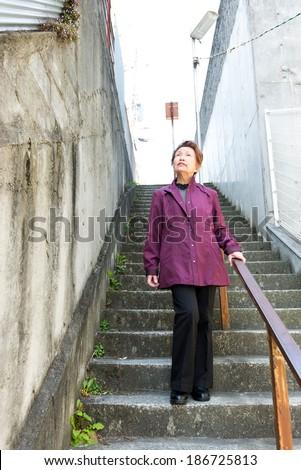 Elderly woman walking the stairs #186725813