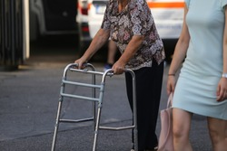 Elderly woman walking with the help of a metal walker