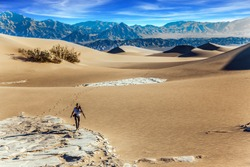 Elderly woman with a camera and a tripod goes among the dunes. Light sand waves from the desert wind. Mesquite Flat Sand Dunes, Death Valley, California. Concept of active and photo tourism
