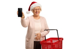 Elderly woman with a shopping basket and a mobile phone wearing a santa claus hat isolated on white background