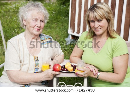 elderly woman with adult daughter sitting in the garden and breakfast