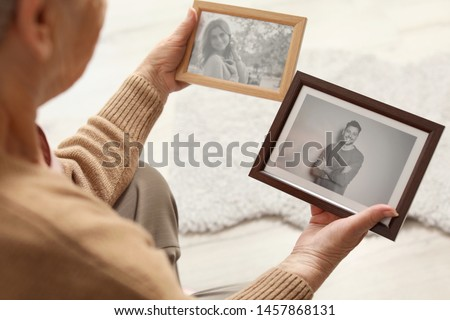 Elderly woman with framed photos at home