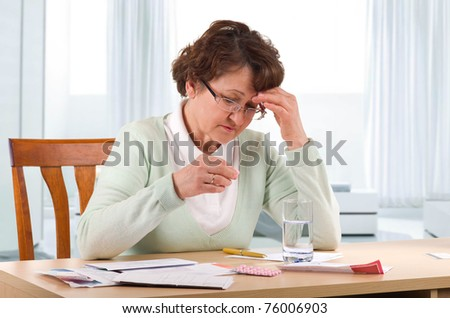 Elderly woman with headache worry about bill notice.