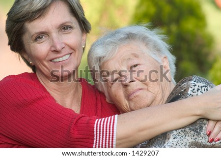Elderly woman with her daughter hugging each other.