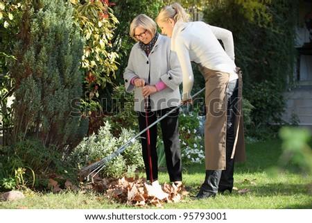 Elderly woman with her gardener - stock photo