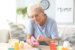 Elderly woman with medicines at home