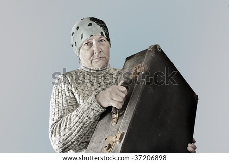 Elderly woman with old suitcase.