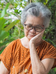 Elderly woman with short white hair toothache standing in garden. Asian senior woman unhealthy and have negative thoughts on life make her unhappy. Concept of health care and mental