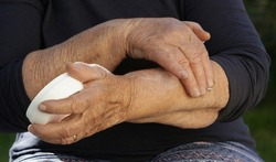 Elderly woman with very dry skin applying moisturizing lotion on her arms