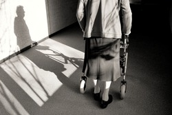 Elderly woman with walker in a hallway, black and white