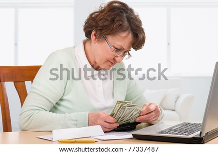 Elderly woman with wallet of money worry about bill notice.