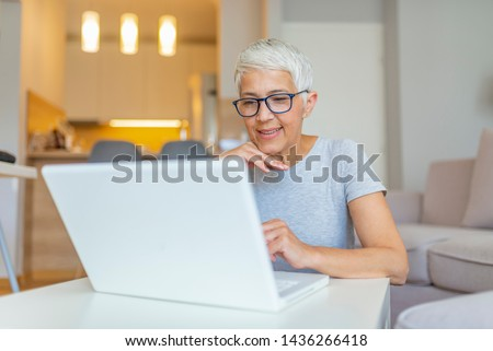 Elderly woman working on laptop computer, smiling. Woman Working From Home On Laptop In Modern Apartment. Trendy woman working on laptop from home