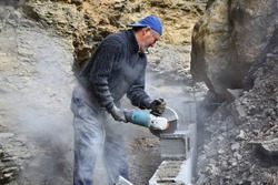 Elderly worker cutting concrete blocks with radial, during the construction of a wall.
