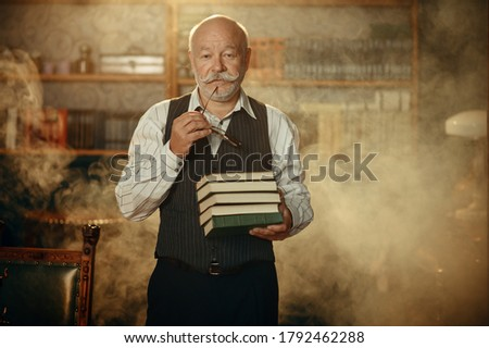 Elderly writer holds stack of books in home office Foto d'archivio ©