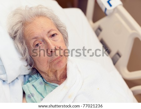 Elderly 80 year old woman with Alzheimer's disease in a hospital bed.