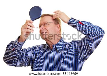Eldery man watching his receding hair line in mirror