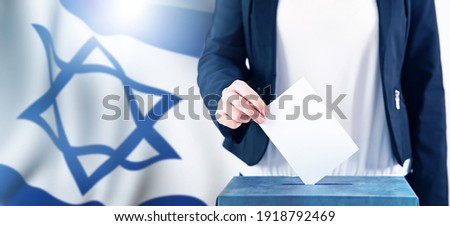 Election in Israel. Hand of a woman putting her vote in the ballot box. Waved Israel flag on background. Stockfoto ©
