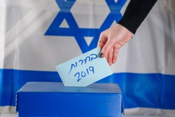 Election in Israel - voting at the ballot box. The hand of woman putting her vote in the ballot box. Israeli Flag on background. Hebrew text Elections 2019.